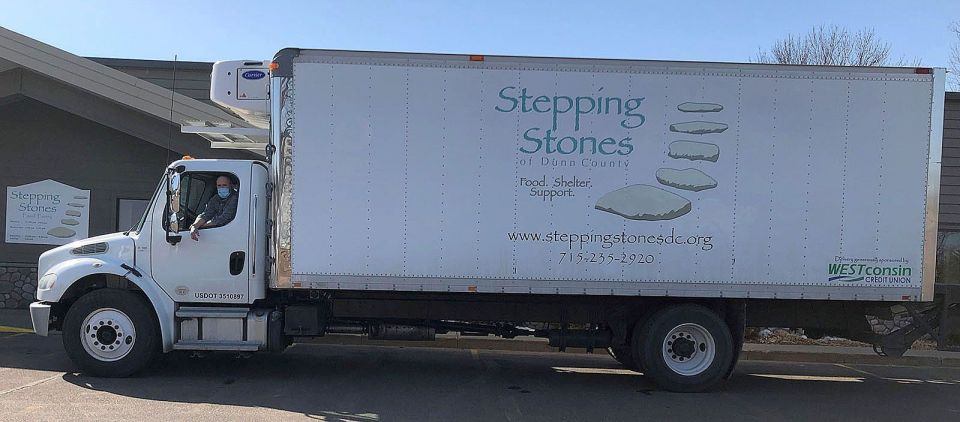 Executive Director Padraig Gallagher takes the wheel of the recently purchased 2014 Freightliner now emblazoned with Stepping Stones of Dunn County's distinctive logo.